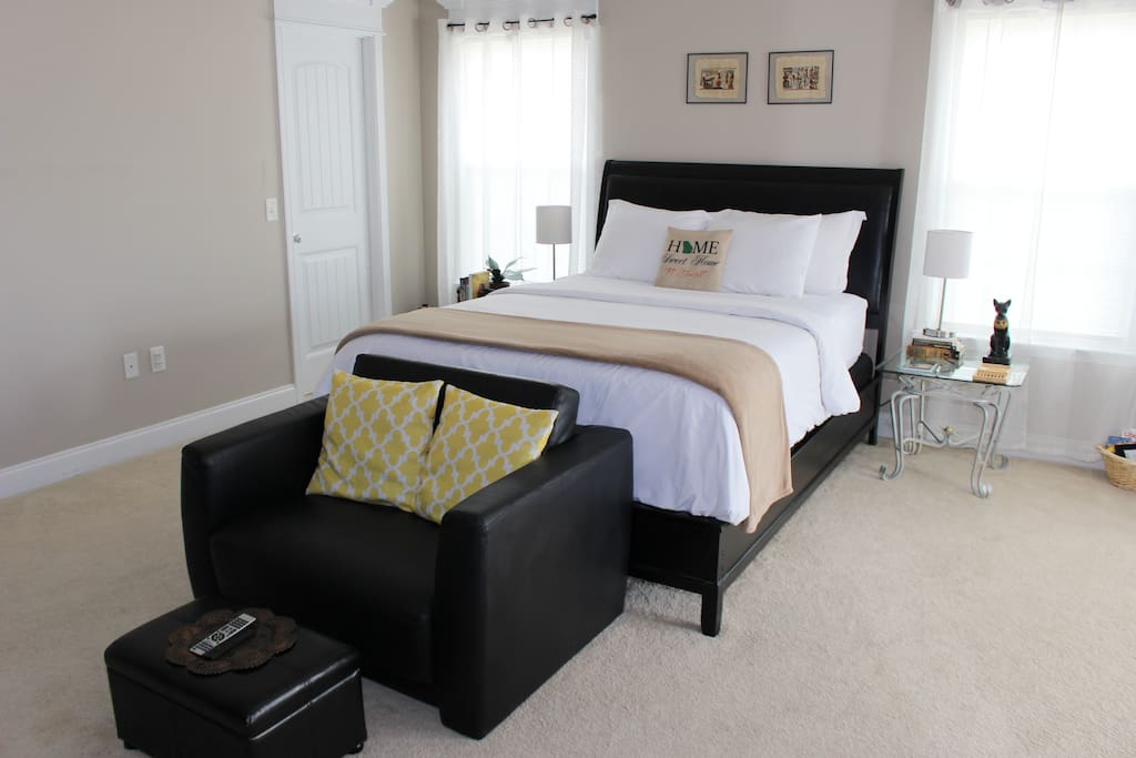 Very comfortable Simmons Beautyrest queen-sized bed with stylish leather headboard and a large leather TV chair at the end.