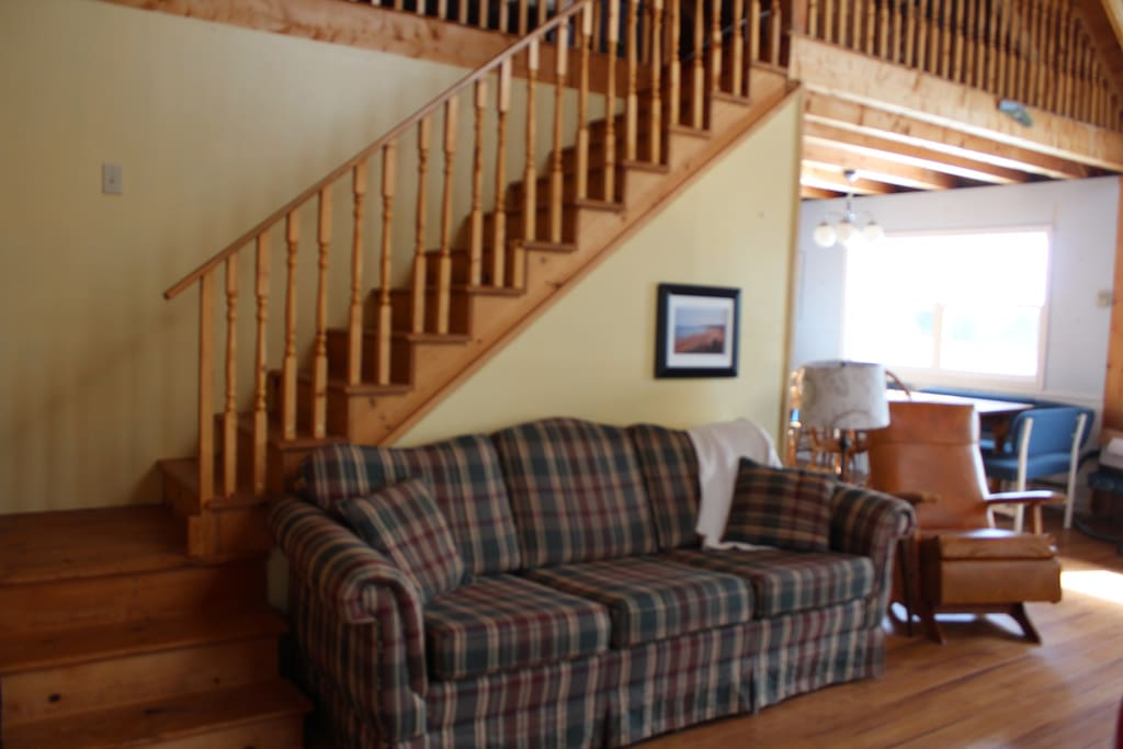 Living area and stairs to the loft, open concept kitchen.