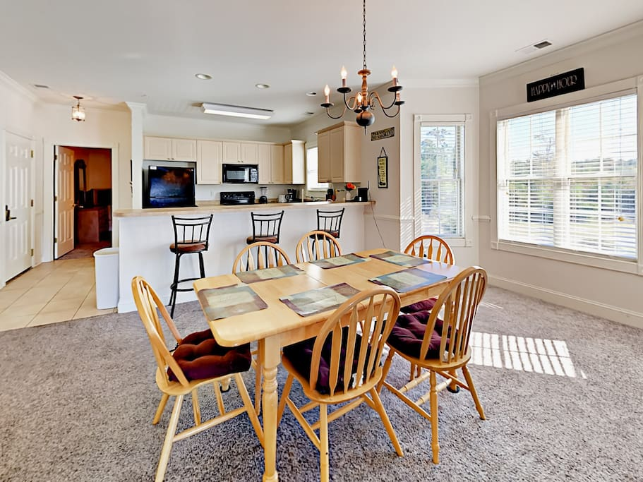 Light and bright dining area with 6-person table and 3 additional seats at the kitchen bar.