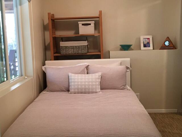 Bedroom with full size bed and dresser. Washer and dryer in closet.