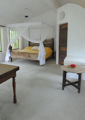 Spacious bedroom with king size double bed, comfortable mattress, cotton sheets and mosquito netting on windows and bed