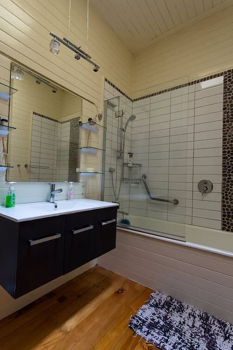 Spacious modern bathroom with bathtub, shower and toilet. There is also a second shower and toilet that can be used- not captured in photo