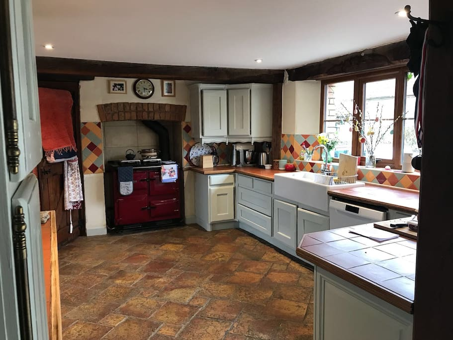 Colourful kitchen open plan with conservatory and oak table eating areas