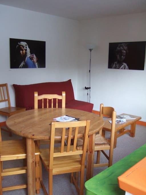 Salon avec deux canapés-lits, table basse, table à manger