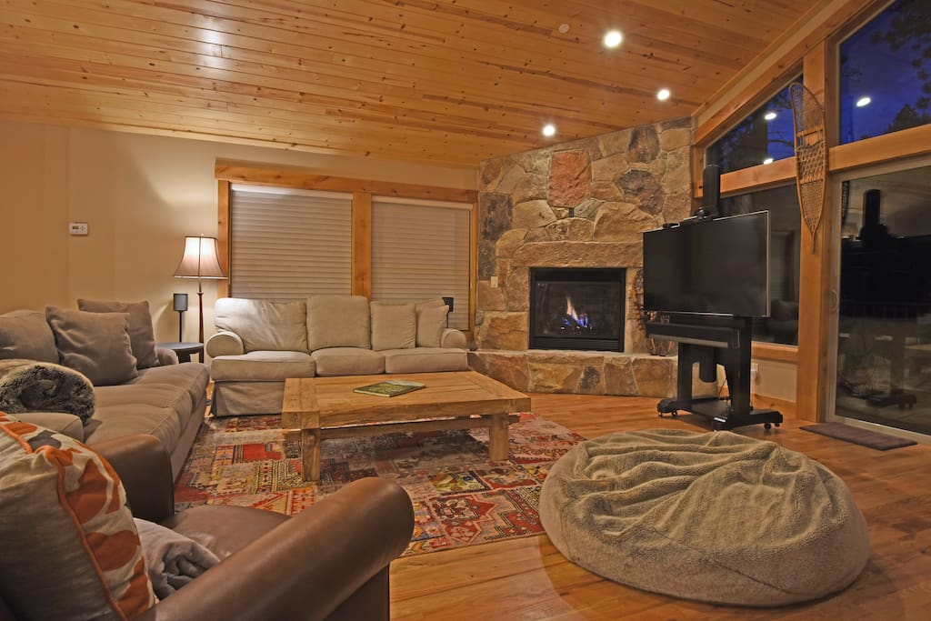 Living room, with fireplace, flat screen TV, and access to the deck
