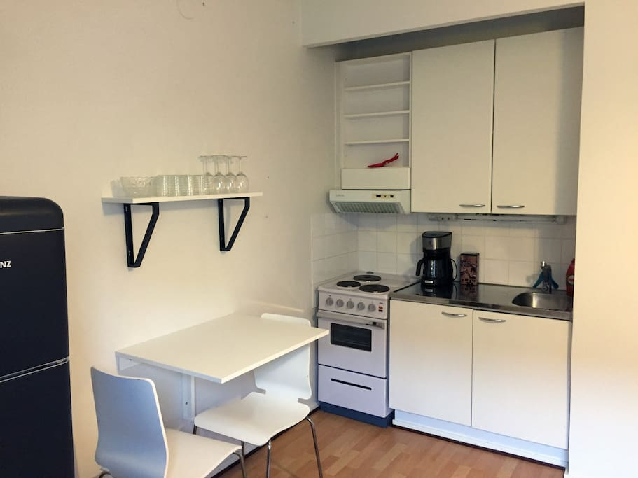Kitchenette has a small dining table and it's equipped with a micro wave oven, a stove, a coffee maker, an electric kettle and a toaster.