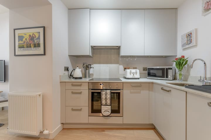 Stylish and modern kitchen with all mod-cons, including electric oven, dishwasher, washing machine, toaster and kettle.