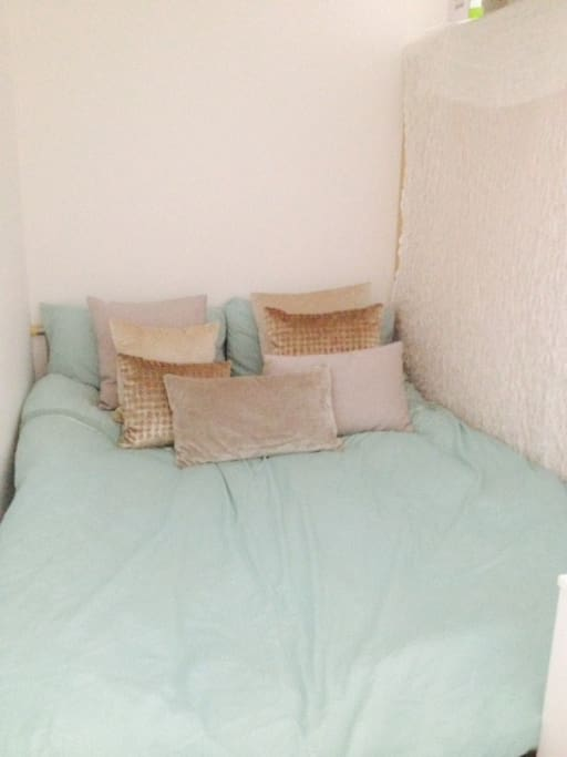 Cosy bed area dressed in bespoke scattered cushion which you can spread around and create a cosy sitting for two