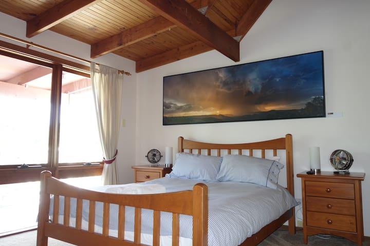 Main bedroom. Balcony with rural views.  TV in room. Outdoor shower.