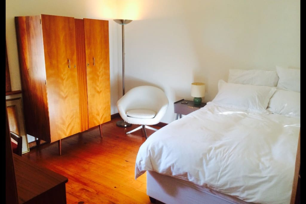Your room, with a retro wardrobe, queen bed, down duvet and Egyptian cotton linen