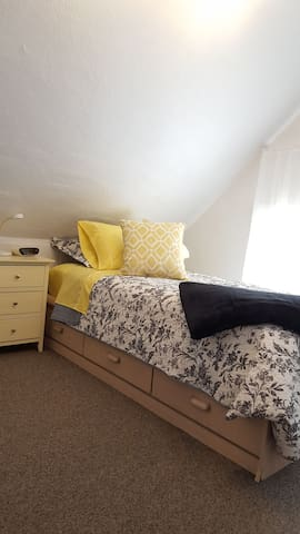 A bright and sunny second bedroom has a single storage bed.