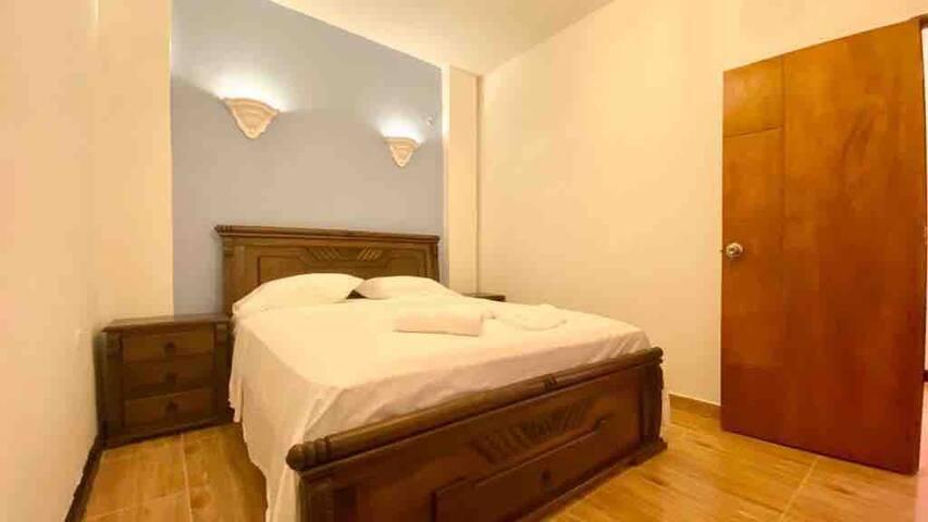 Segunda habitación Cuenta con cama Queen de madera la cual tiene un cajón al final de la cama, dos mesas de noche, accesorio con ganchos para colgar ropa, sofá cama, cajilla de seguridad, nichos de luces tenues y luz colonial, uso de su preferencia
