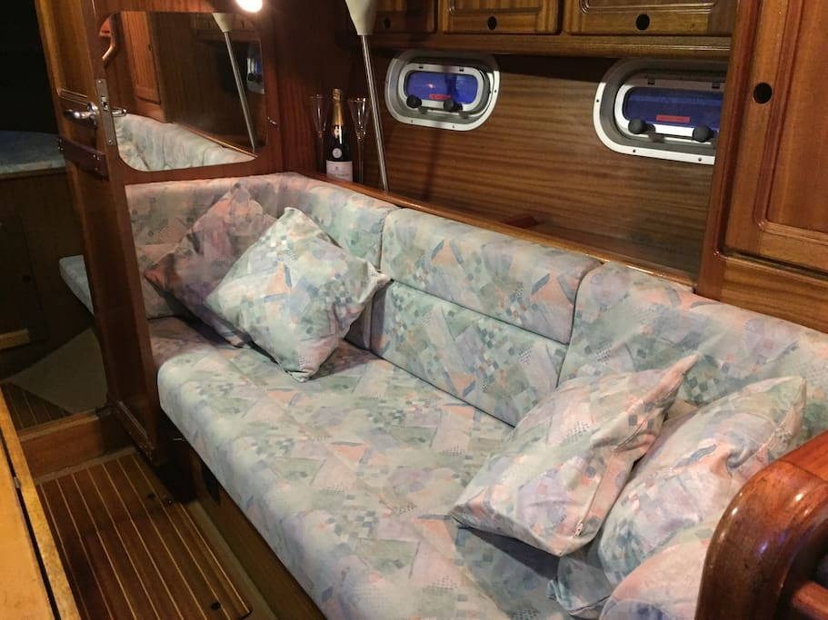 Saloon with fold down teak table. New cushions/covers throughout