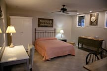 Queen bed with desk, hot plate, and large storage area.
