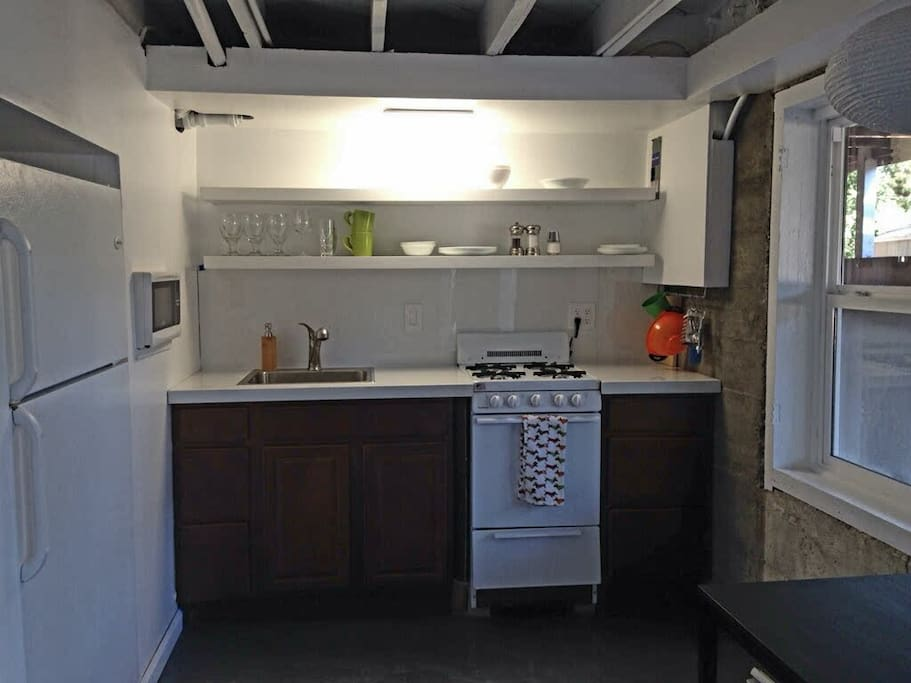 Stocked kitchen with full size refrigerator and dining table