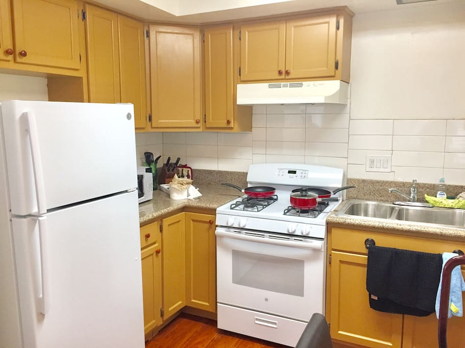 Full size kitchen equipped with a stove, oven, refrigerator/freezer, toaster oven, microwave, and coffee maker.