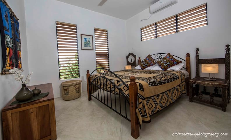 Double bedroom with en-suite bathroom, walk-in wardrobe, decorated with antique African furnishings.