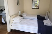 Here's the twin bedroom with two comfy standard single beds. This room is great for children as it is next to the main bedroom. It has a tiled floor, a chest of drawers, a large mirror and double shuttered doors leading into the garden.