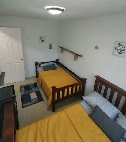 Habitación secundaria con 1 cama matrimonial y una individual, cuenta con aire acondicionado y con pantalla con cable Dish.