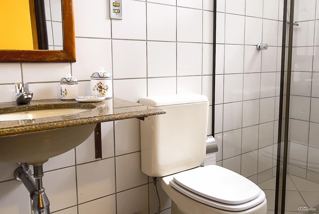 Banheiro da suíte com box blindex e chuveiro elétrico.