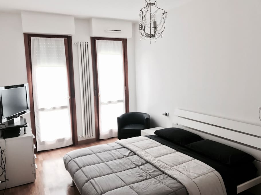 Spacious light bedroom with double bed, TV, air conditioner