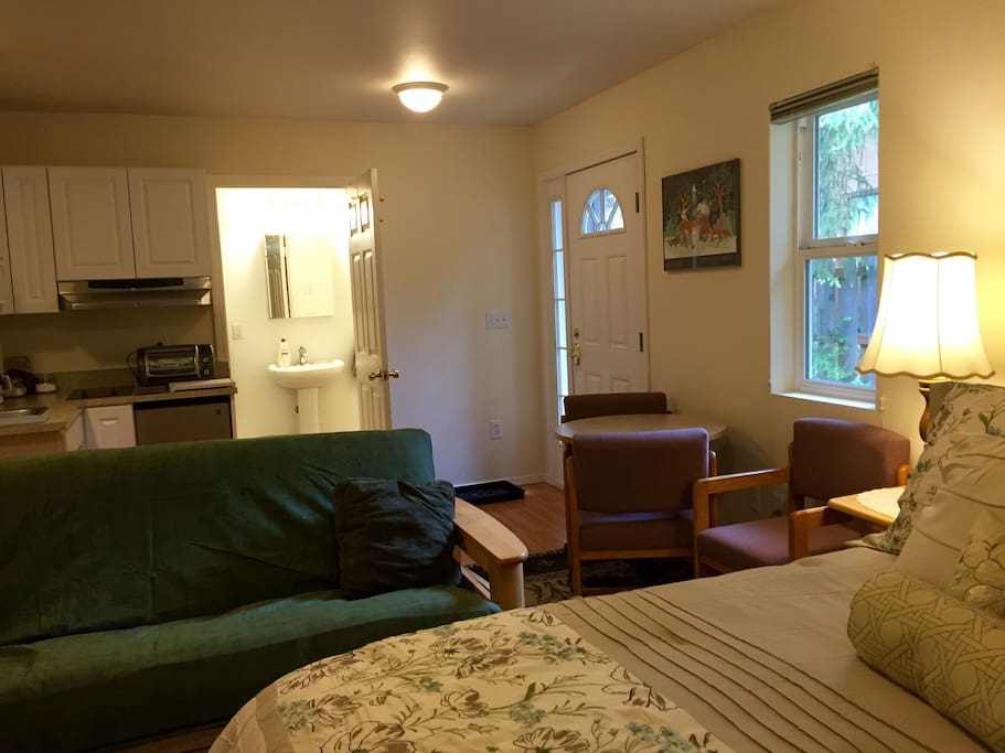 Another view of the bed, futon, table with 3 chairs, kitchen and bathroom.