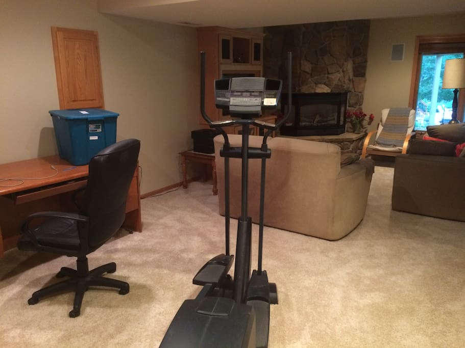 Your own living room, complete with sofas, workout machine, desk and flat screen television