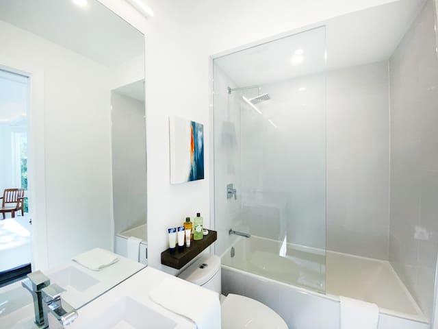 High ceiling, bright bathroom, giant mirror.