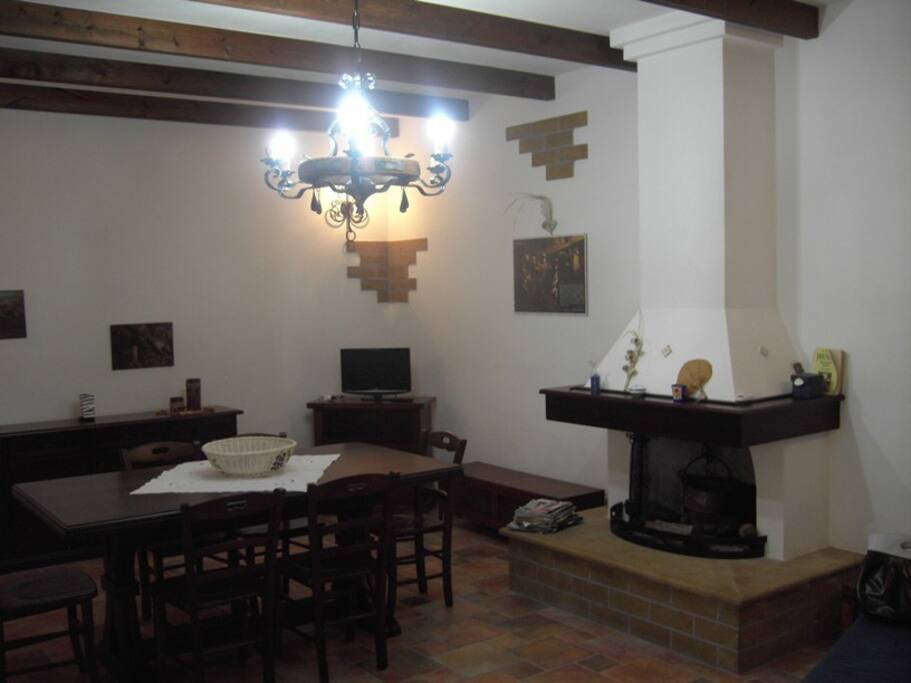 Ampio soggiorno con tavolo in massello di legno allungabile, sedie,cmino e divano letto matrimoniale con rete elettrosaldata e materasso a molle h.16 .
