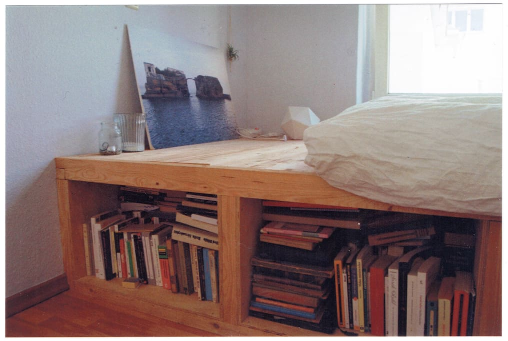 Cosy double bed on a wooden structure next to the window