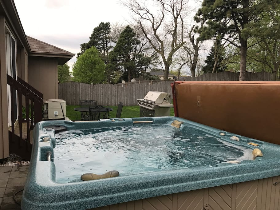 Hot tub to relax in after a long day and BBQ grill on cement patio with table & chairs and a large area with a hill to enjoy!  You will also find large garbage cans out here for your convenience...