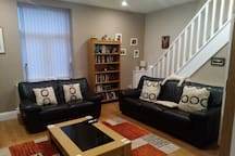 Lounge area with pullout sofabed and stairs leading to bedroom