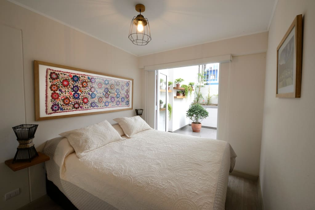 Bedroom. Queen size Rosen bed. The art on the bed is a textile hand-embroidered by artisans of the Peruvian Andes.