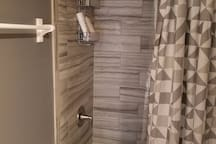 Newly-tiled shower and new modern toilet