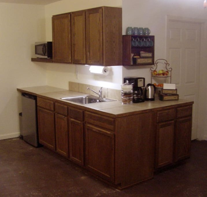 Kitchenette with microwave, toaster, and mini fridge, with hot plates in lower cabinet