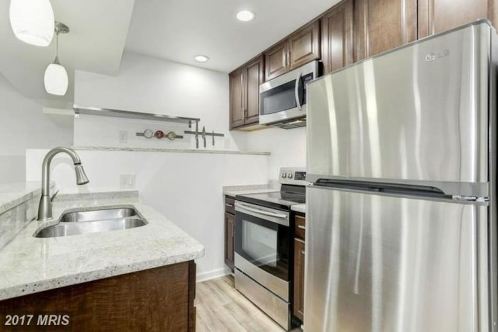 full kitchen with self cleaning oven, pots & pans,  silverware,  plates and other kitchenware