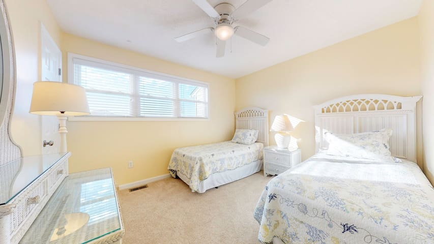 Light and bright upstairs bedroom with two twin beds, wicker dresser, mirror, night stand and plenty of lighting.  Shares a hallway bathroom with queen bedroom across the hall.