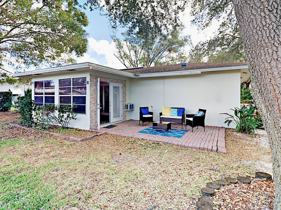 Brick patio with outdoor living room in the private, tree-shaded yard. Your rental is professionally managed by TurnKey Vacation Rentals.