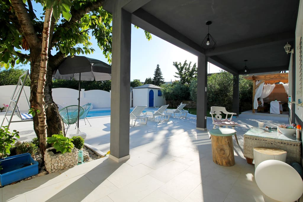 Covered veranda in front of living room with view toward outdoor dining area and pool