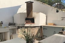 Outdoor kitchen complete with Gas hob, BBQ, large pizza oven, sink and ample workspace.