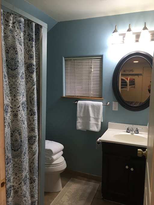 Full bathroom with standup shower stall and fresh linens.