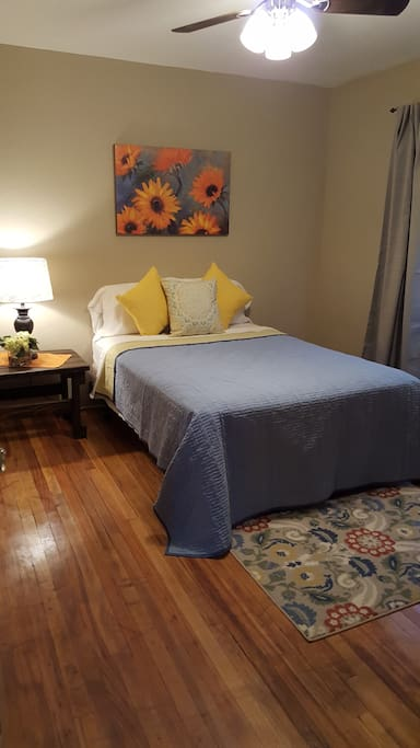 Small bedroom cute and comfy with a dresser and full sized bed
