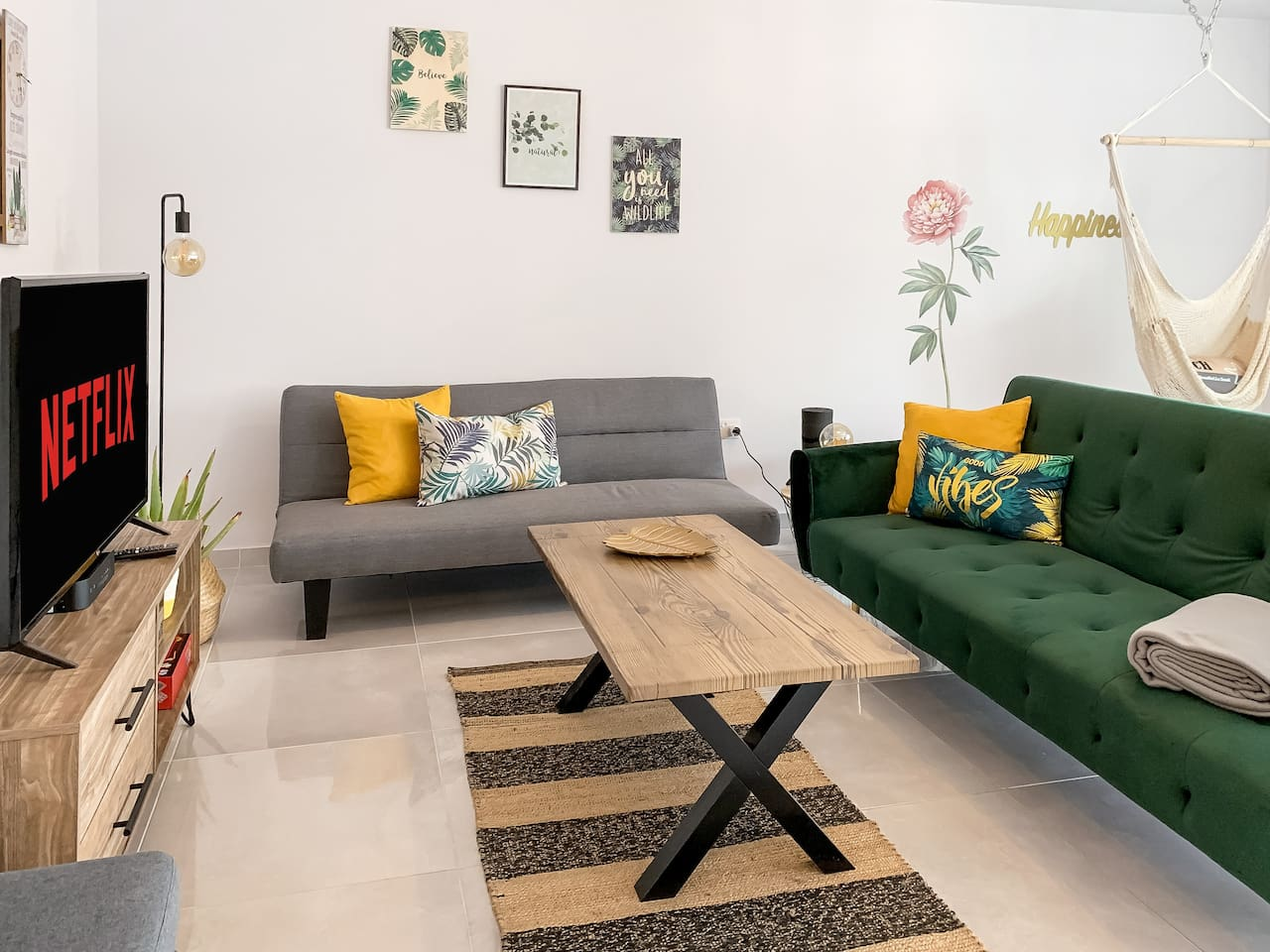 "Stylish Living Room with two comfortable sofa beds, hanging chair and a large 43"" Flatscreen TV"