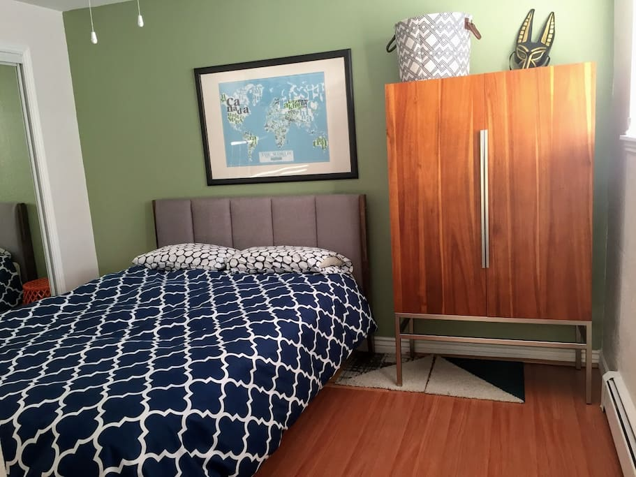 The bed is on a modern mid-century frame with a beautiful wardrobe with a built-in mirror. The closet next to the bed has a large full length mirror.