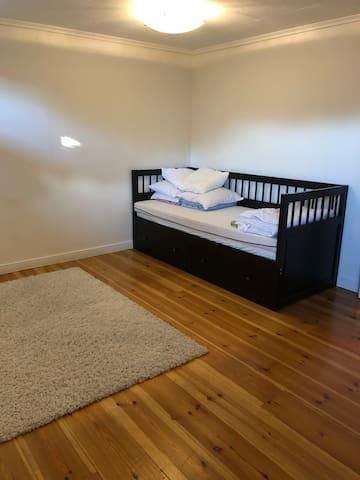 Stort sovrum i källaren med en bäddsoffa och en tresits-soffa (passar som sovplats för ett barn)  Rummet har även en öppen spis med gnistskydd.