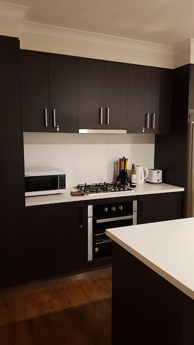 Shared kitchen with microwave, big fridge/freezer, kettle, toaster, pots and pans, dishes and utensils