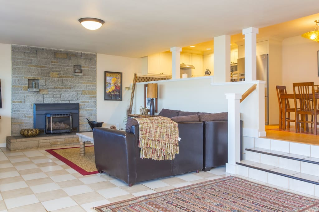 An L-shaped couch faces a gorgeous stone fireplace in the living area.