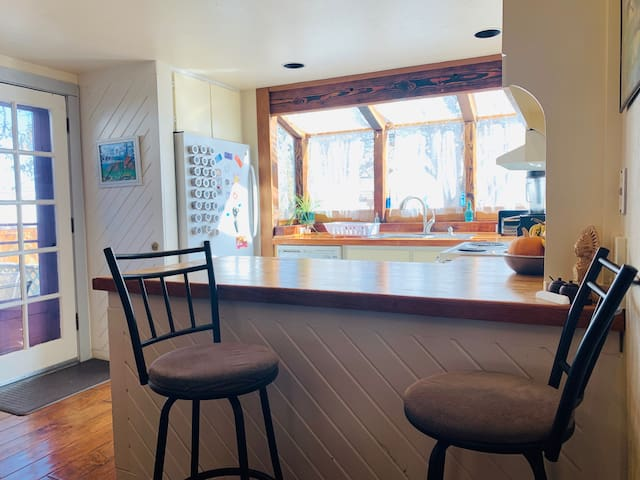 Barstools looking over our light-filled kitchen with skylight windows.