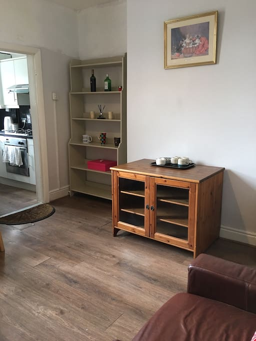 Livening room has dinning table,  chairs, fridge, freezer, leather armchair, tea set and tea bags.