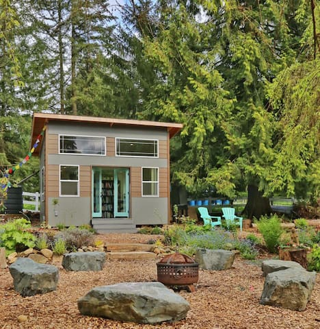 Nestled into a garden, this tiny house structure is cozy and cute.